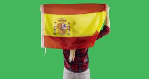 A spanish flag on the back of a woman on chroma key green screen. Flag of Spain fluttering in the wind stock video footage