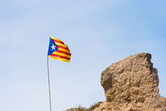 The Spanish flag Estelada on the mountain, over blue sky background, Catalunya, Spain. Copy space for text. The Spanish flag Estelada on the mountain, over blue Royalty Free Stock Image