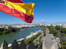 Spanish flag fluttering with city and river in background, Seville, Spain Stock Photos