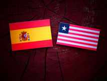 Spanish flag with Liberian flag on a tree stump isolated. Spanish flag with Liberian flag on a tree stump Royalty Free Stock Images