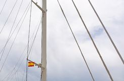 Spanish flag in mast of large sailing yacht. Against overcast sky in Mallorca, Spain Stock Photo