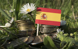 Spanish flag with stack of money coins with grass royalty free stock image