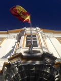 Spanish flag weaving. Over a whitewashed building. Low angle stock photos