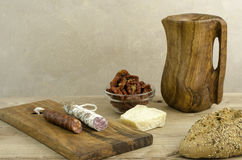Spanish fuet, chorizo, bread, parmesan, and olive wooden cutting board and pitcher. Stock Photo