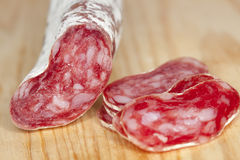 Spanish fuet salami cuts on wooden board Stock Images