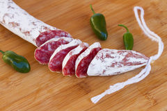 Spanish fuet sausage. Spanish  fuet sausages with green peppers on wooden table Stock Photos