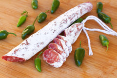 Spanish fuet sausages with green peppers Royalty Free Stock Photos