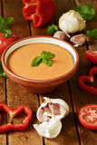 Spanish gazpacho on a wooden table. An earthenware bowl with spanish gazpacho and some vegetables to prepare it such as tomato, red pepper or garlics on a rustic Stock Photos