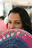 Spanish Girl with Fan at Feria. Spanish girl gazes from behing her fan Royalty Free Stock Photos