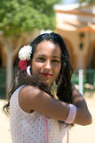 Spanish Girl in Feria Dress adjusts hair. Spanish girl with carnations in hair sand a traditional pink polka dot feria dress smiles at viewer with sun casting stock images