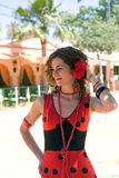 Spanish Girl in red flamenco dress. Spanish girl with carnations in hair adjust her attire. She is wearing a red flamenco dress with black polka dots at the stock photos