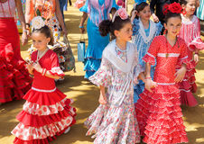 Spanish girls in traditional dress walking alongside Casitas at the Seville Fair. Stock Photos