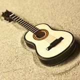 Spanish guitar in the sand. Golden colors Royalty Free Stock Images