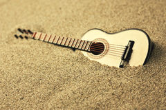 Spanish guitar in the sand. Golden colors Stock Photography