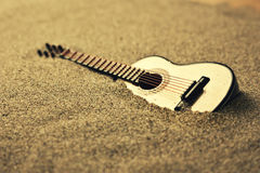 Spanish guitar in the sand. Golden colors Royalty Free Stock Image