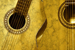 Spanish Guitars. Two spanish guitars side by side in golden sepia royalty free stock images