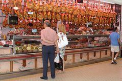 Couple buys delicious Spanish ham Iberico at the market, Valencia, Spain Stock Photo