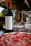 Spanish ham jamon and bottle of red wine. On restaurant table Royalty Free Stock Image