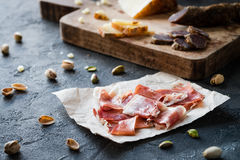 Spanish ham jamon serrano or Italian prosciutto crudo with sliced Italian hard cheese pecorino toscano, homemade dried meat salami Stock Image
