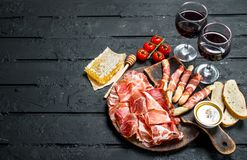Spanish ham with red wine and breadsticks royalty free stock photography