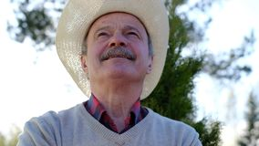 Spanish senior man in hat relaxing outdoor. Spanish happy senior man in hat relaxing standing outdoor dreaming about future plans stock footage