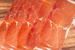 Spanish jamon iberico sliced. On wooden background Royalty Free Stock Images