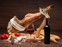 Spanish Jamon Serrano on wooden table jamonera with tomatoes, spices, glass and bottle of red wine. Home cooking, food photo concept. Horizontal close up image royalty free stock images