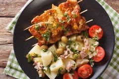Spanish kebab Pinchos Morunos and salad Patatas Alinadas close-up. Horizontal top view royalty free stock photo