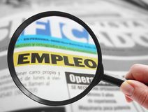 Spanish language job search. Person using a magnifying glass to look at a Spanish language newspaper classified employment  empleo Stock Image