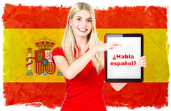 Spanish language learning concept. Young woman holding tablet pc. National flag of Spain at the background. Spanish language learning concept. Collage. Clip-Art Royalty Free Stock Image