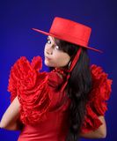 Spanish look. Young Spanish flamenco dancer posing in a red dress and hat Royalty Free Stock Images