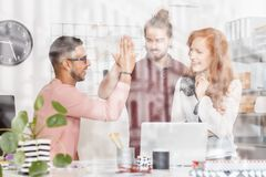 Spanish man and team lead. Spanish men and team lead giving a high five in business office royalty free stock photos