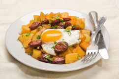 Spanish meal with sliced chorizo, roasted potato and fried egg Royalty Free Stock Images