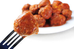 Spanish meatballs stew. A meatball in a fork and a plate with a spanish meatballs stew on a white background Stock Photo