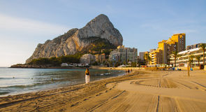 Spanish Mediterranean Beach, Calpe, Costa Blanca. Young pretty and fit women walking along the sandy beach coast in Calpe, Spain, Costa Blanca, PEnon de Ifach in Royalty Free Stock Photography