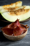 Spanish melon con jamon, serrano ham with melon. Closeup of a bowl with some slices of serrano ham and some pieces of melon in a plate to prepare the typical Stock Image