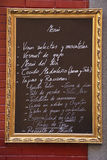Spanish Menu. Spanish language menu written on blackboard surrounded by gold frame against red brick wall Royalty Free Stock Photo