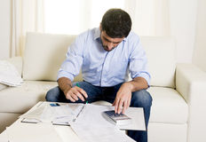 Spanish mexican business man worried paying bills on couch Stock Photos