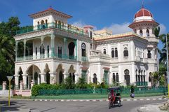 Spanish-Moorish palace in Cuba. Passenger tricycle taxi making turn in front of Palacio de Valle Valle`s Palace in Punta Gorda in Cienfuegos, Cuba royalty free stock image