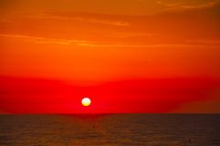 Spanish morning sun on red sky with yellow clouds by the Mediter. Ranean sea in July Stock Photo