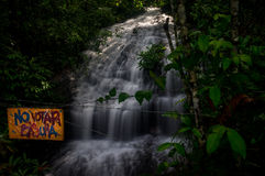 Spanish no littering sign in front of waterfall. Colombia in December 2015: A Spanish sign reading No Votar Basura urges the visitor of a beautiful waterfall not Stock Photo