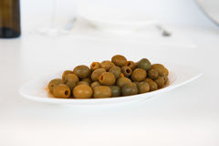 Spanish olives on the white plate. Tipical spanish olives on the white plate Royalty Free Stock Image