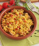Spanish paella in a clay plate. On the napkin Royalty Free Stock Image