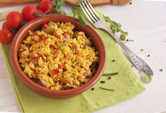 Spanish paella in a clay plate. With tomatoes Royalty Free Stock Photos