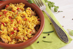 Spanish paella in a clay plate. With tomatoes Stock Photo
