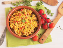 Spanish paella in a clay plate. With tomatoes Stock Images