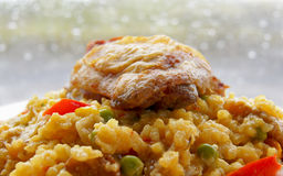 Spanish Paella and Golden Fried Chicken thigh against rainy window background Royalty Free Stock Image
