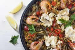 Spanish paella in a pan. Seafood paella in a pan with fish on top with lemons and parsley stock photography