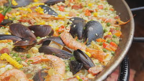 Spanish paella with yellow rice, shrimps and mussels cooking at the food market. Street food festival. Traditional. Spanish paella with yellow rice, shrimps and stock video