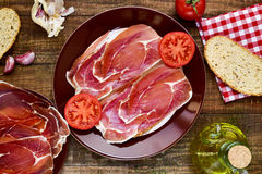 Spanish pan con tomate y jamon, bread with tomato and serrano ha. High-angle shot of a plate with spanish pan con tomate y jamon, sliced bread topped with tomato Royalty Free Stock Images